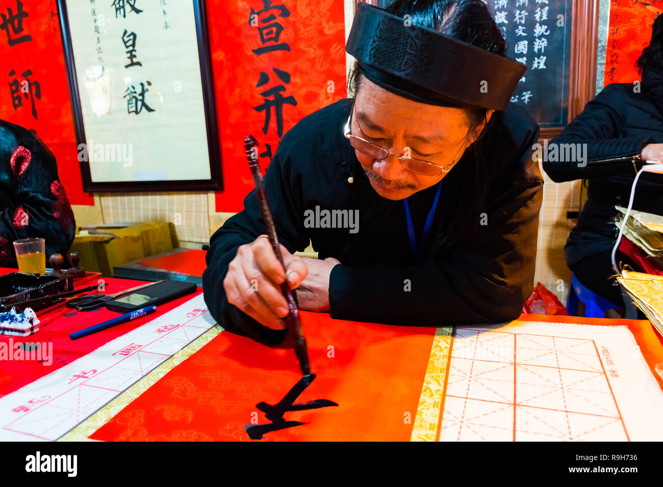 HANOI, VIETNAM, FEB 14, 2018: Old master is writing ancient letter for everyone in lunar new year in Hanoi, Vietnam. This is a tradition of vietnamese - Stock Image