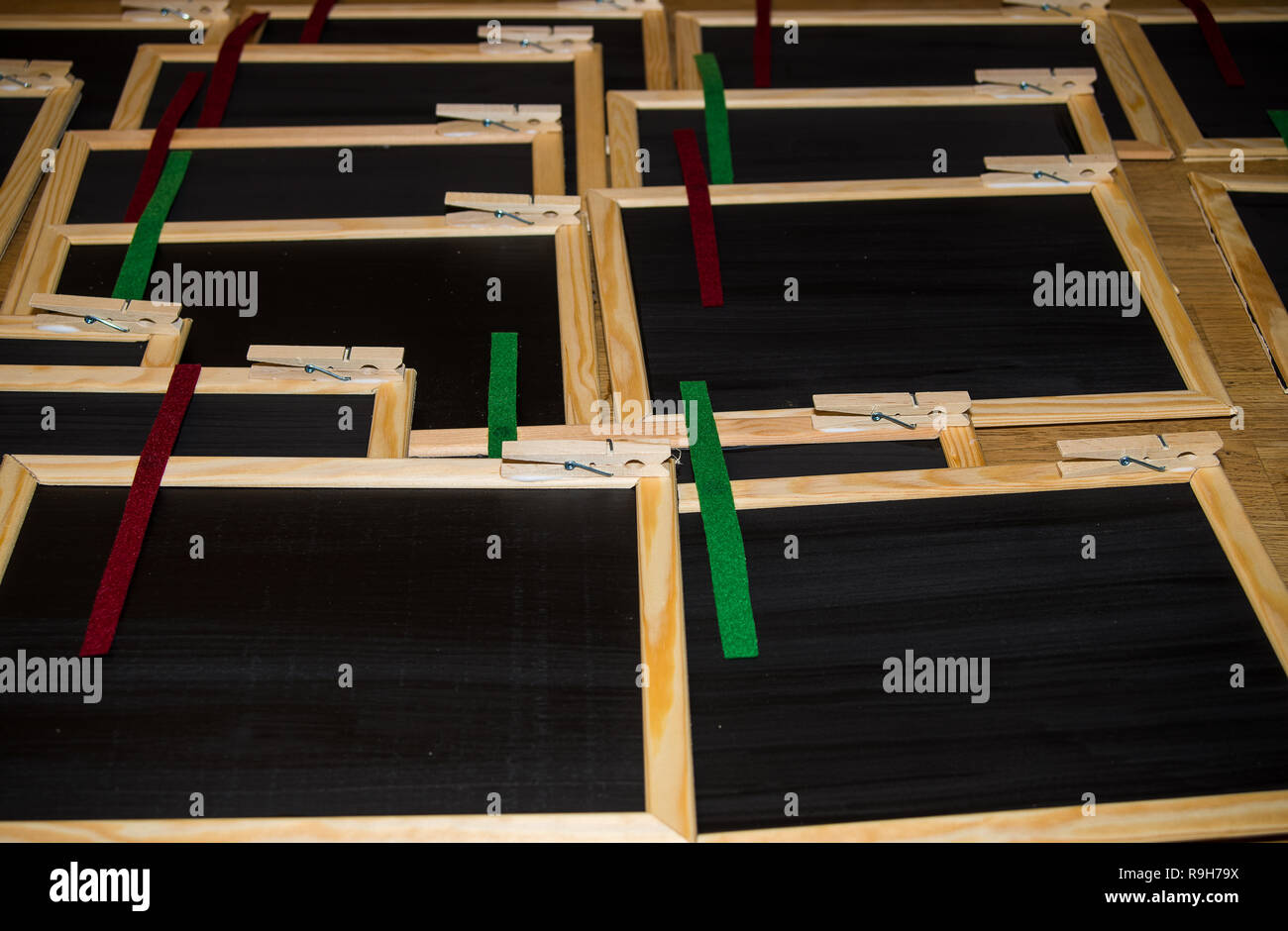 Small blackboards decorated with felt ribbons lie on a table - Stock Image