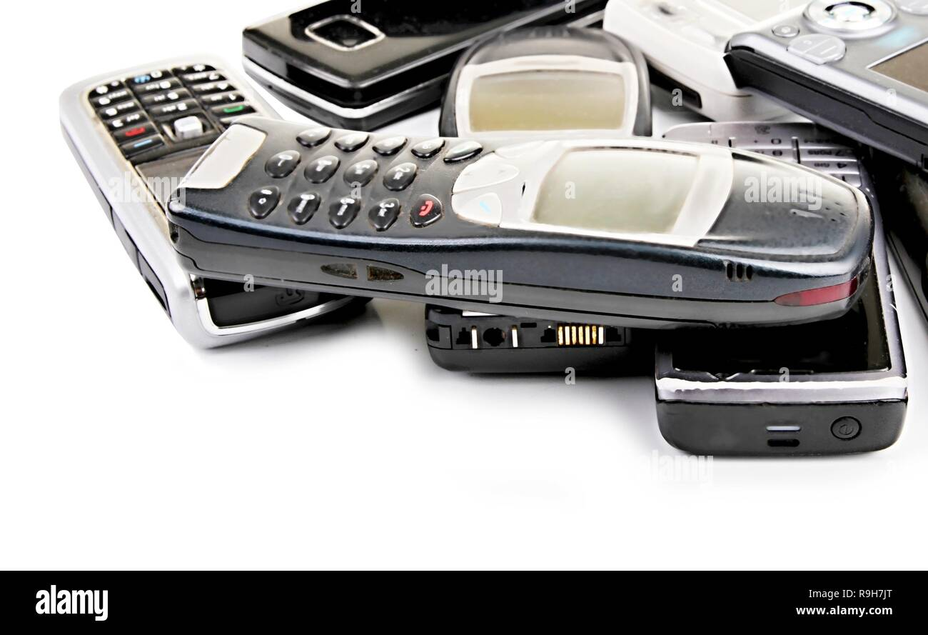 old mobile phones piled up on a table with white background no people stock photo Stock Photo