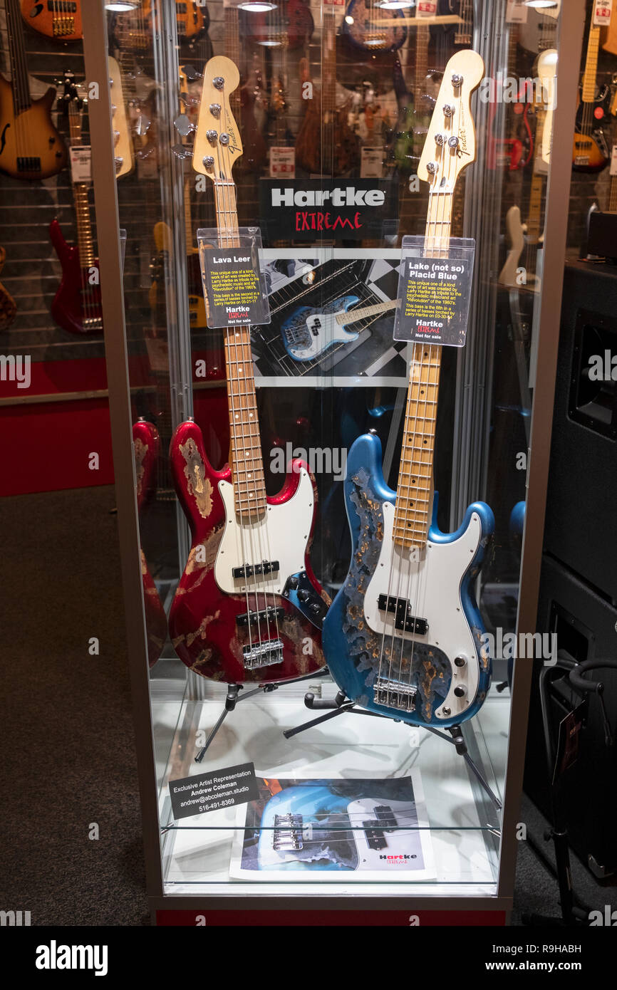 A display of 2 very rare one of a kind Larry Hartke decorated Fender bass guitars displayed at Sam Ash music store on West 34th Street in Manhattan. - Stock Image