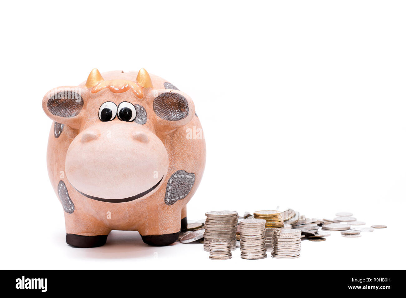 Piggy bank and coins stacked up over white background. Stock Photo