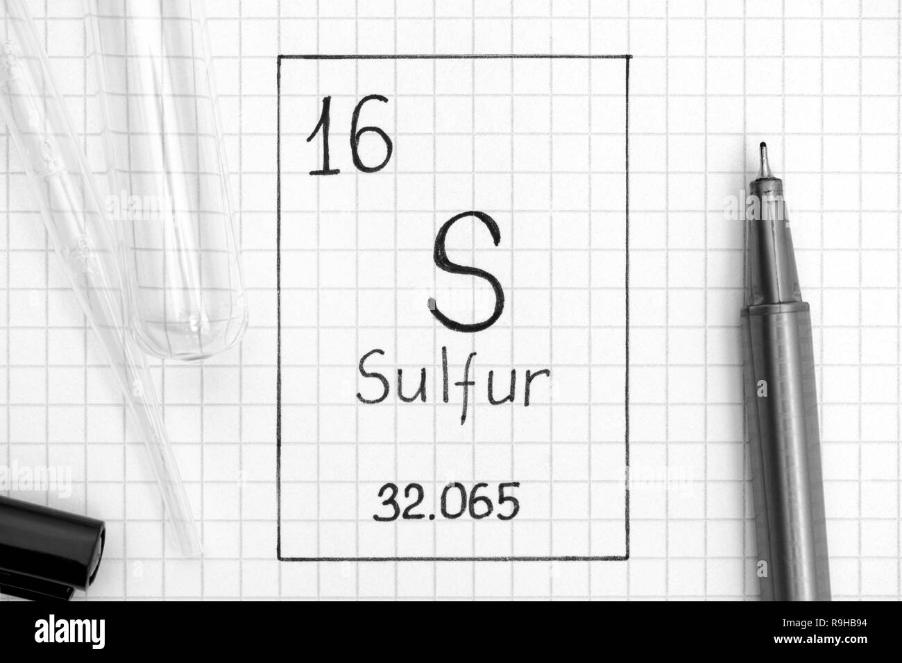 The Periodic table of elements. Handwriting chemical element Sulfur S with black pen, test tube and pipette. Close-up. Stock Photo