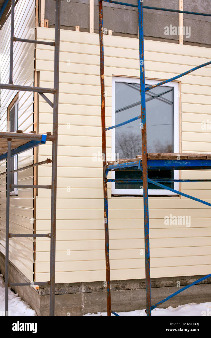 Beige siding covering the wall and scaffolding around house. - Stock Image