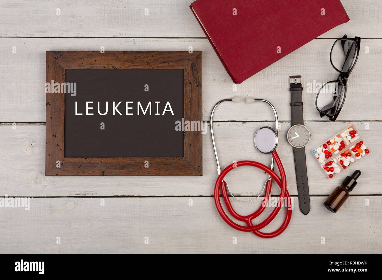 Medecine concept - blackboard with text 'Leukemia', pills, book, eyeglasses, watch and stethoscope on white wooden background - Stock Image