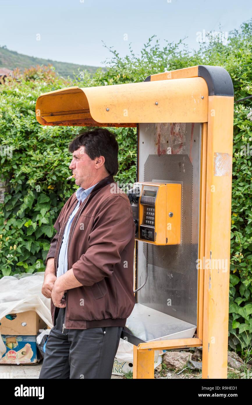 Man smoking by telephone kiosk Prenjass village Albania - Stock Image