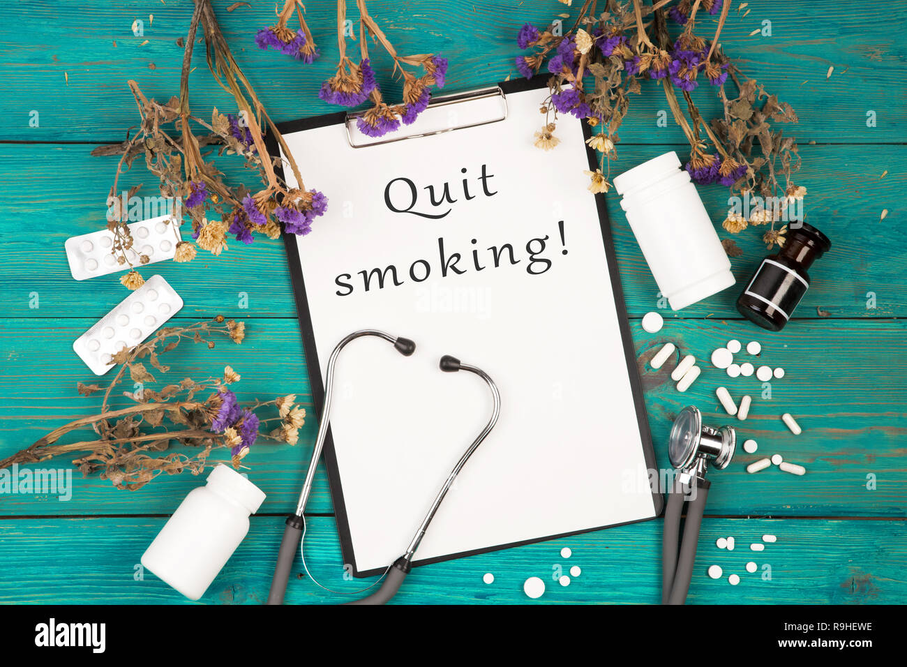 Workplace of doctor - stethoscope, medicine clipboard with text 'Quit smoking!', bottle and pills on blue wooden table - Stock Image