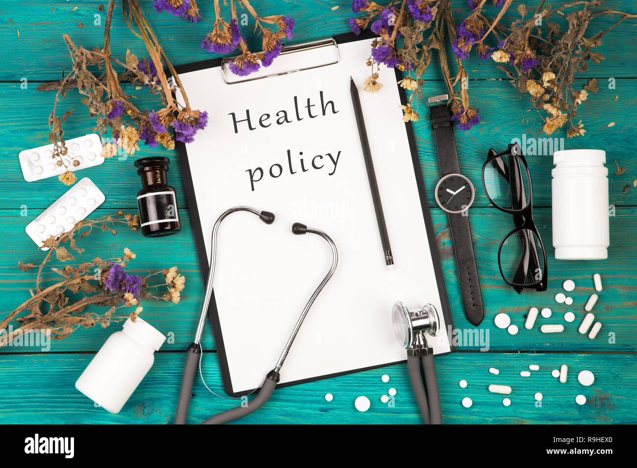 Workplace of doctor - stethoscope, medicine clipboard with text 'Health policy', bottle, glasses, watch and pills on blue wooden table - Stock Image