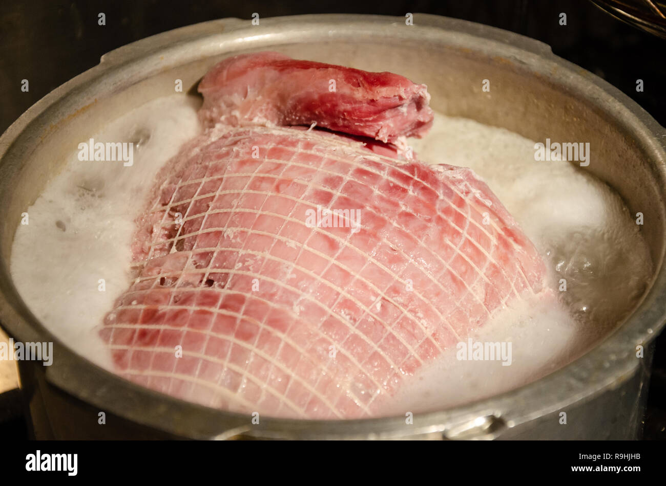 A joint of gammon boiling in a large pan on a hob. - Stock Image