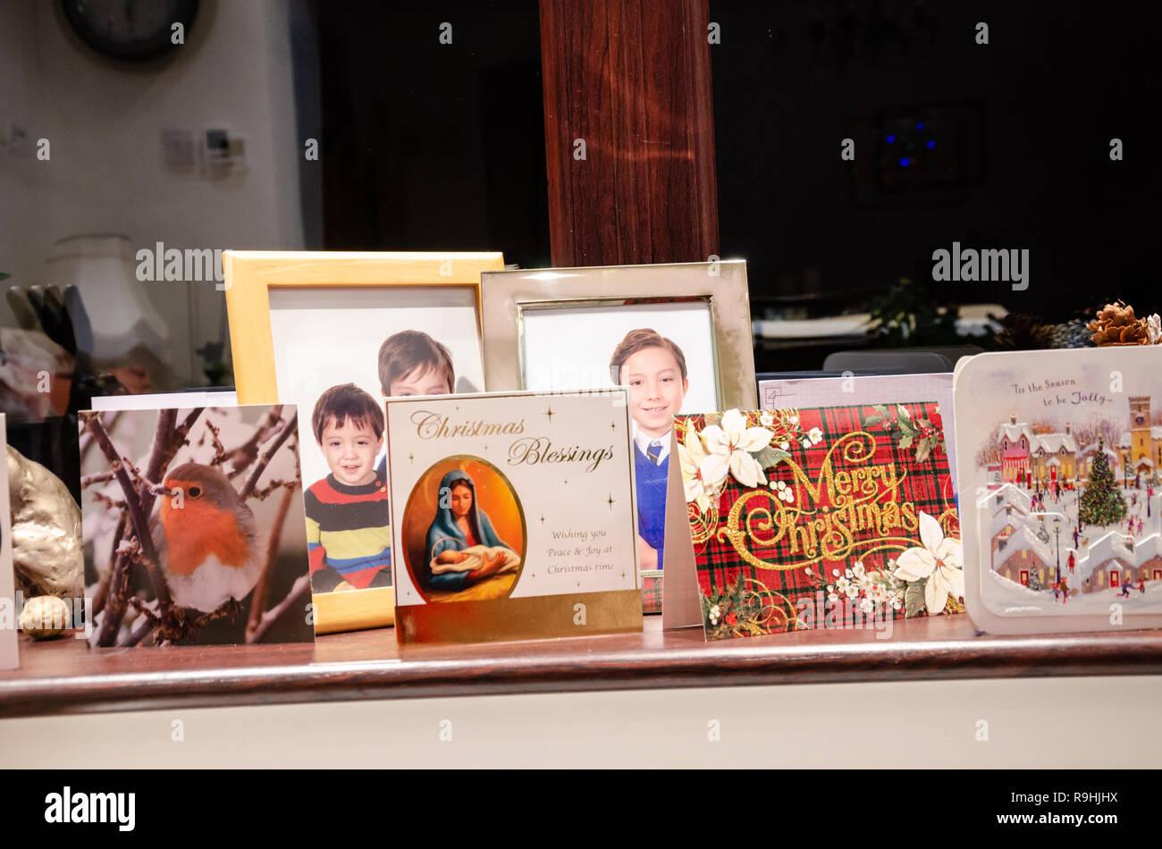 Seasonal Christmas cards on a window sill alongside family photos. - Stock Image