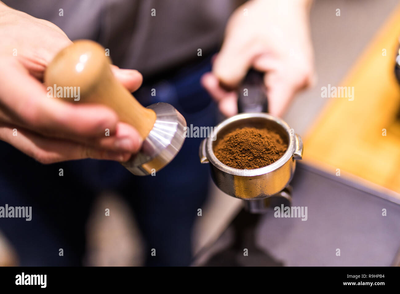 Man is using a tamper to press freshly ground morning coffee into a coffee tablet Stock Photo