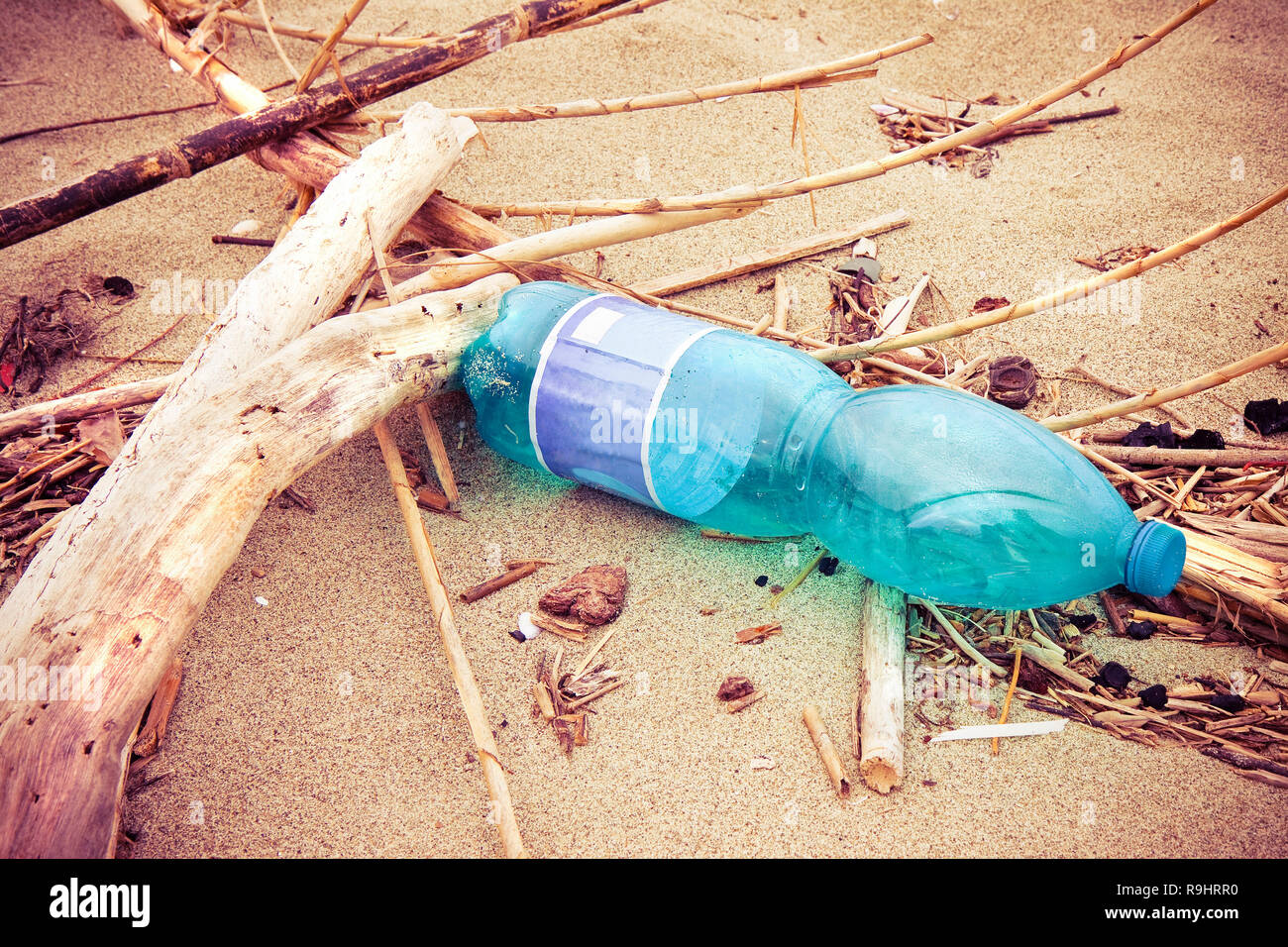 Empty green plastic bottle abandoned on the beach - plastic waste problem - Stock Image