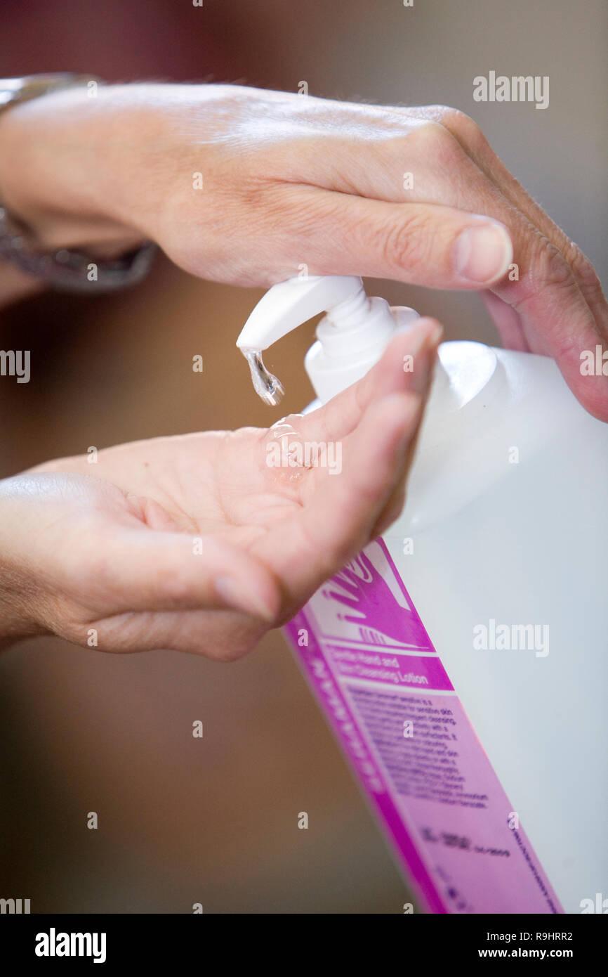 Female hands using hand sanitizer gel pump dispenser in a hospital healthcare environment - Stock Image