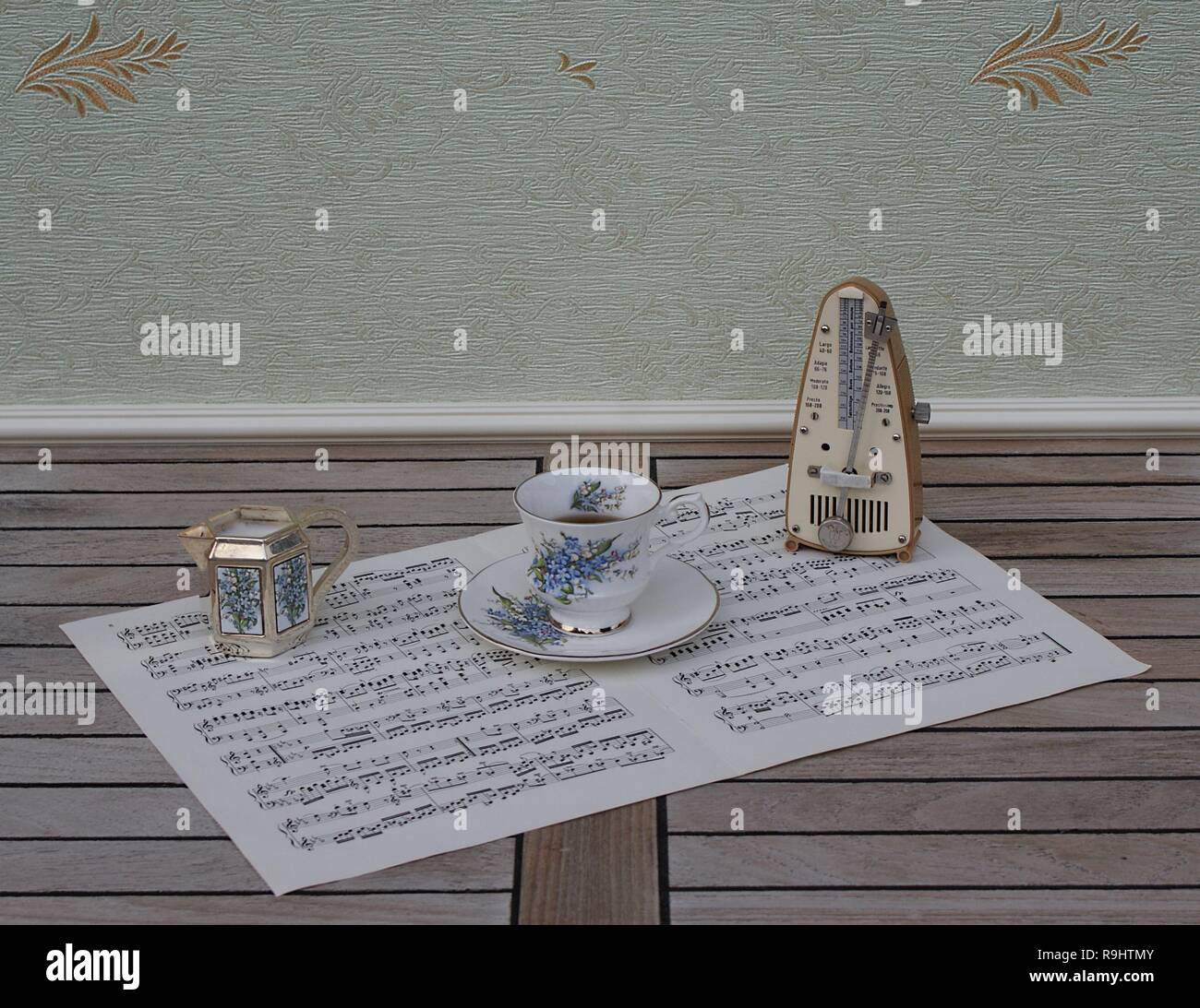 English teacup and saucer, cream jug, with floral decor, and metronome for music on a sheet of music Stock Photo