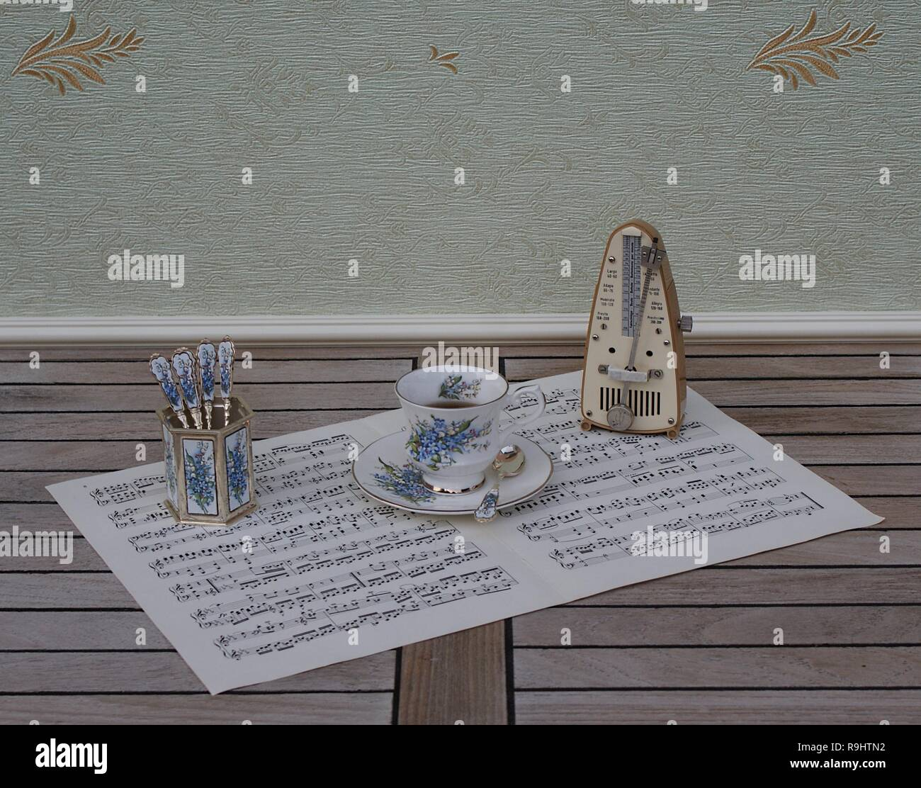 English teacup and saucer, spoon vase and teaspoon, with floral decor, and metronome for music on a sheet of music - Stock Image
