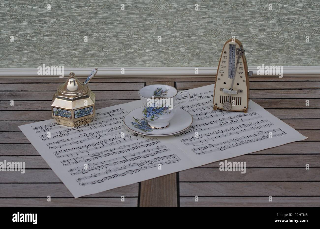 English teacup and saucer, sugar bowl and sugarspoon, with floral decor, and metronome for music on a sheet of music - Stock Image