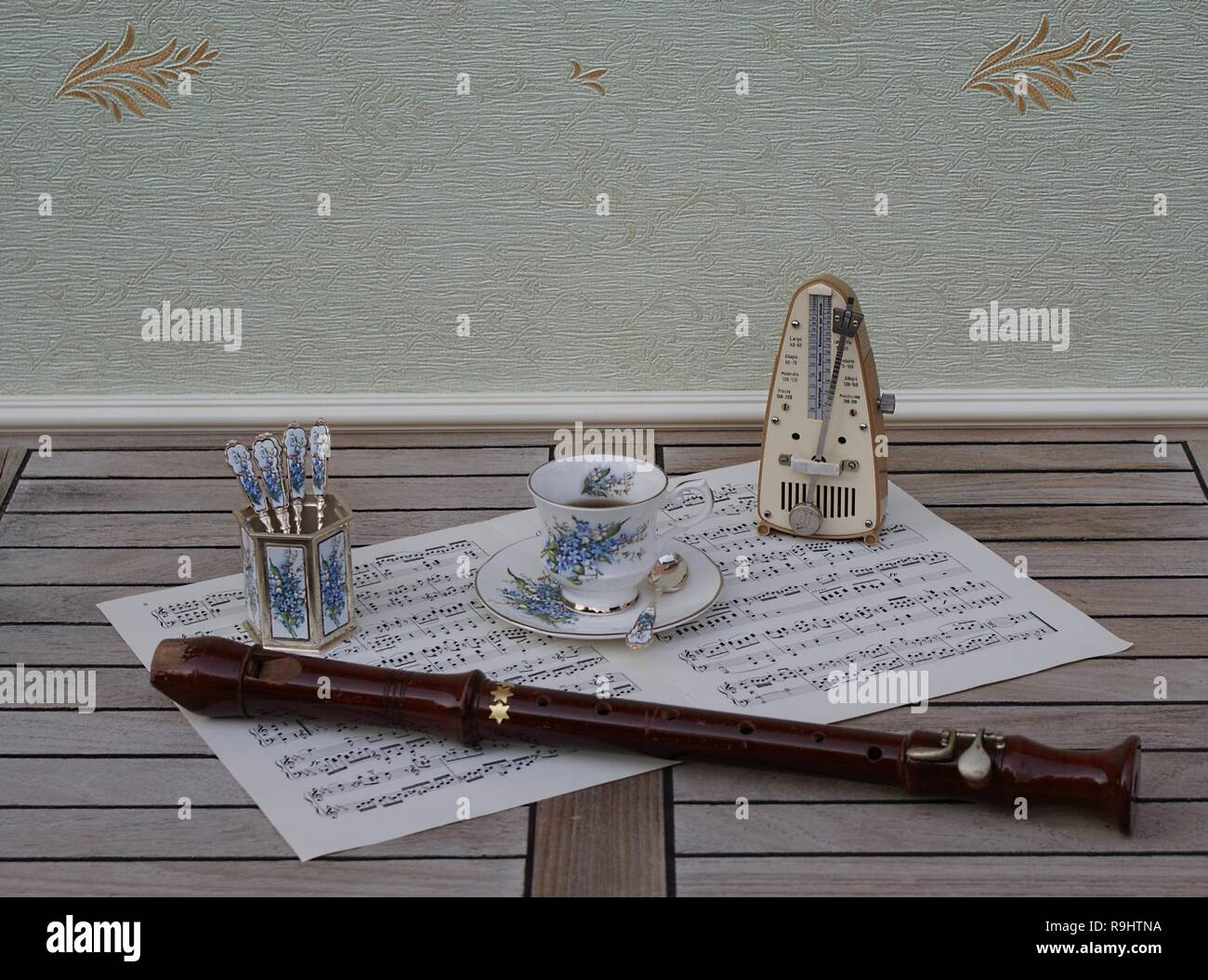 English teacup and saucer, spoon vase and teaspoon, with floral decor, and metronome for music and a block flute on a sheet of music - Stock Image