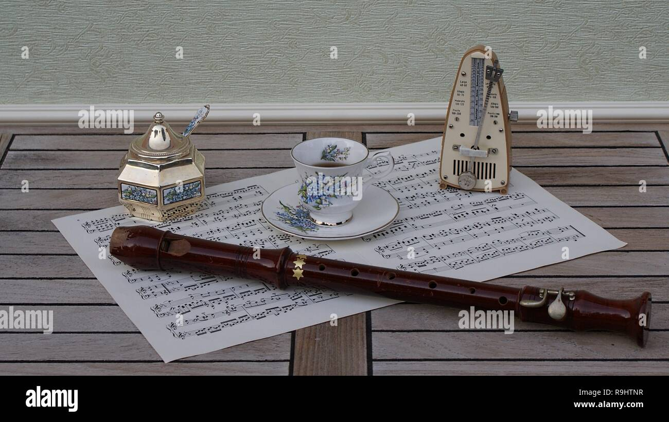 English teacup and saucer, sugar bowl and sugarspoon, with floral decor, metronome for music and a block flute on a sheet of music - Stock Image
