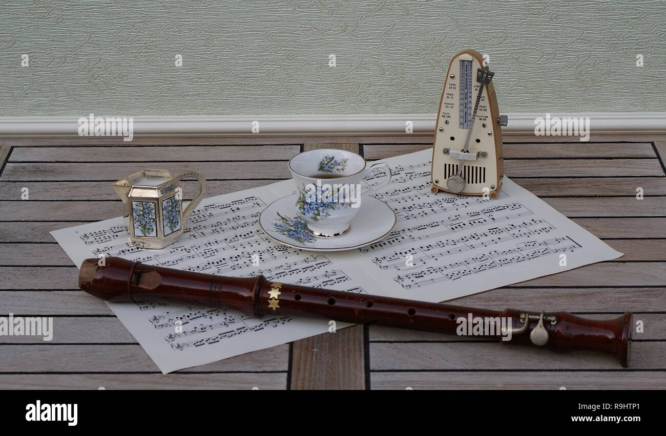 English teacup and saucer, cream jug, with floral decor, metronome for music and a block flute on a sheet of music - Stock Image