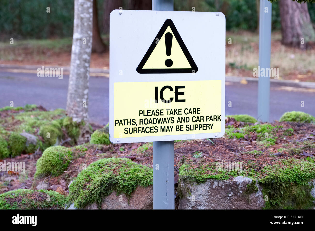 Ice winter road weather take care sign warning slippery surface - Stock Image