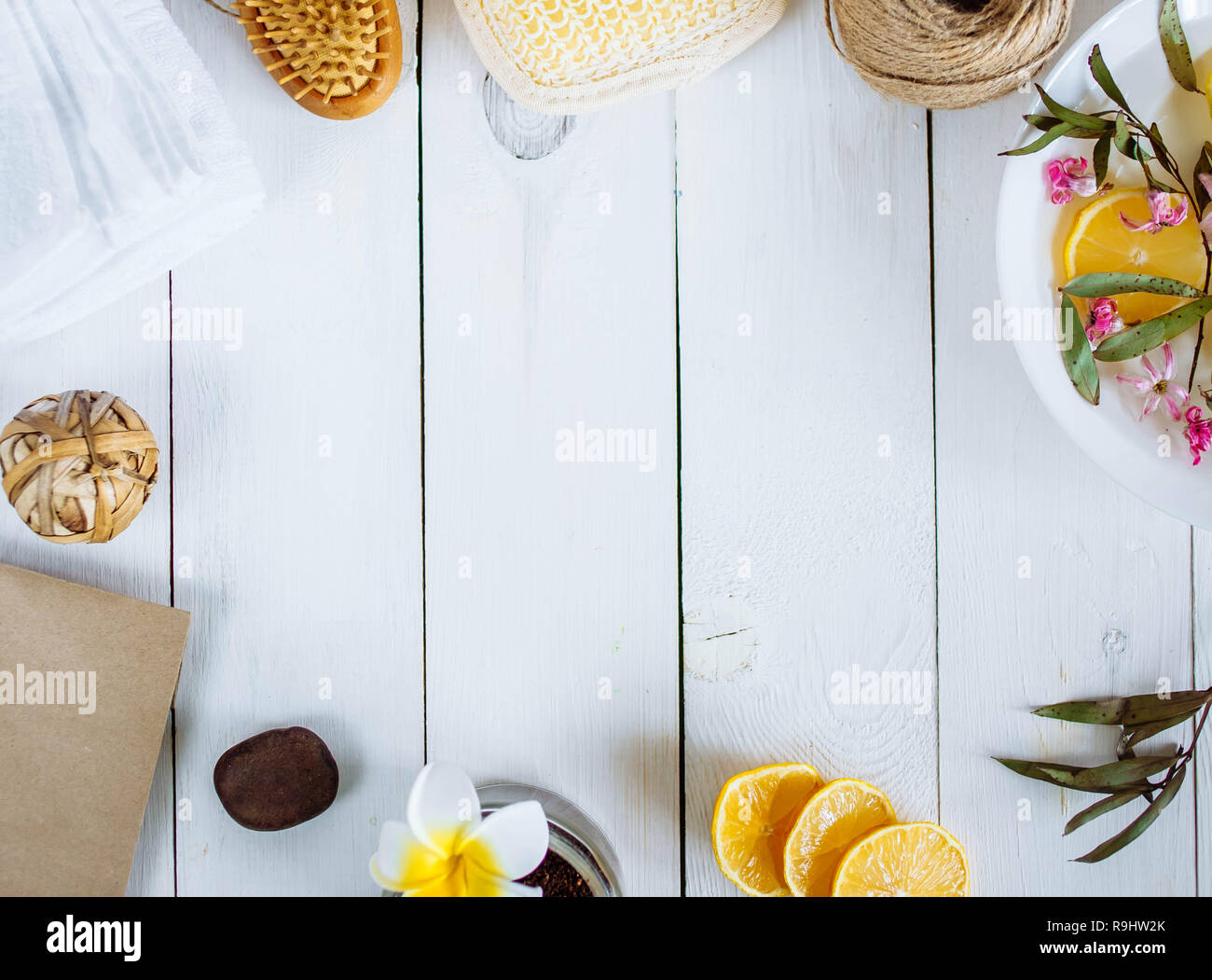 Homemade lemon essential oil, salt bath and fresh honey in the plate with honeycomb, dipper and mints on rustic background from top view. Flat lay goo Stock Photo