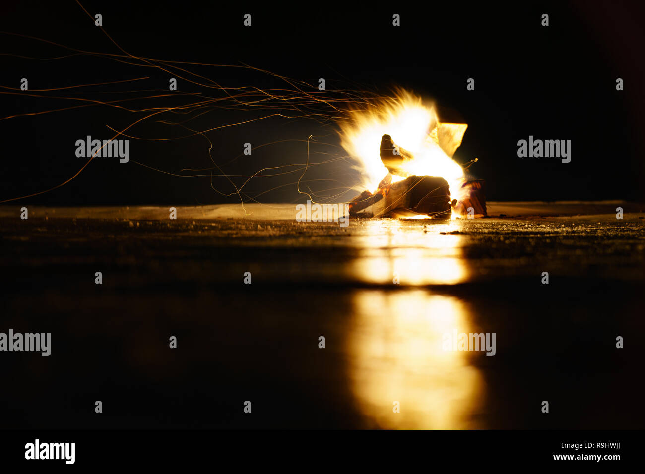 Camp fire reflection on ice at night - Stock Image