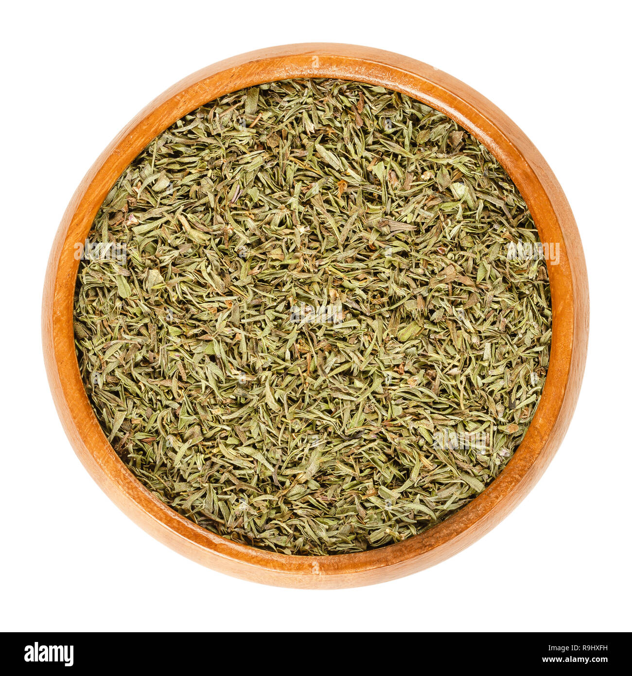 Dried savory in wooden bowl. Chopped summer savory, Satureja hortensis, a herb and seasoning for barbecues, stews and sauces. - Stock Image