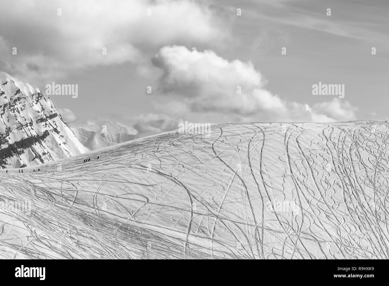 Snowy off piste slope for freeriding with traces from skis, snowboards and silhouette of freeriders at sunny winter day. Caucasus Mountains, Georgia,  - Stock Image