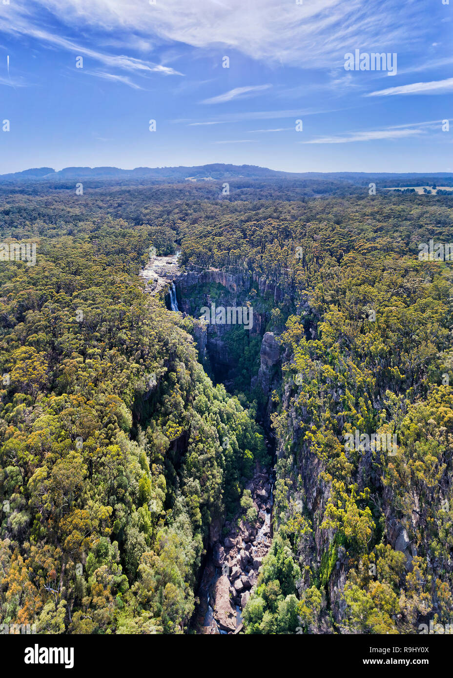 Deep creek eroded by Kangaroo river falling from flat plateau as Carrington Fall down to source of Kangaroo valley in the middle of gum-tree forest in - Stock Image