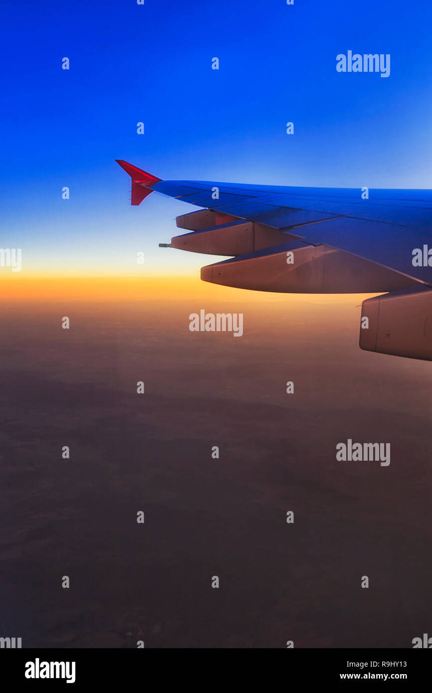 East and distant horizon at sunrise seen high in the sky from on board of flying airplane and fragment of wing with jet engines. - Stock Image