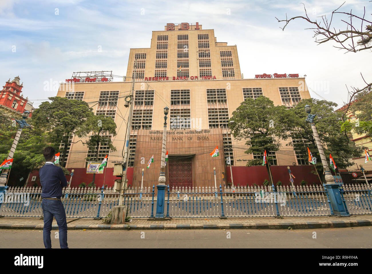 Young man looking at the Reserve Bank of India building at Dalhousie area of Kolkata with view of early morning city road - Stock Image