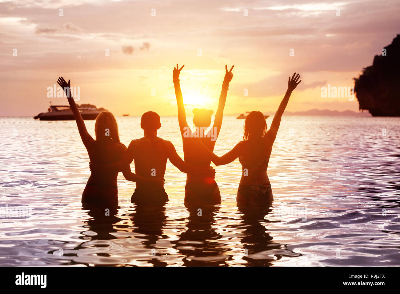 Four happy friends are meeting sunset at sea beach standing in water and hugging with raised arms Stock Photo