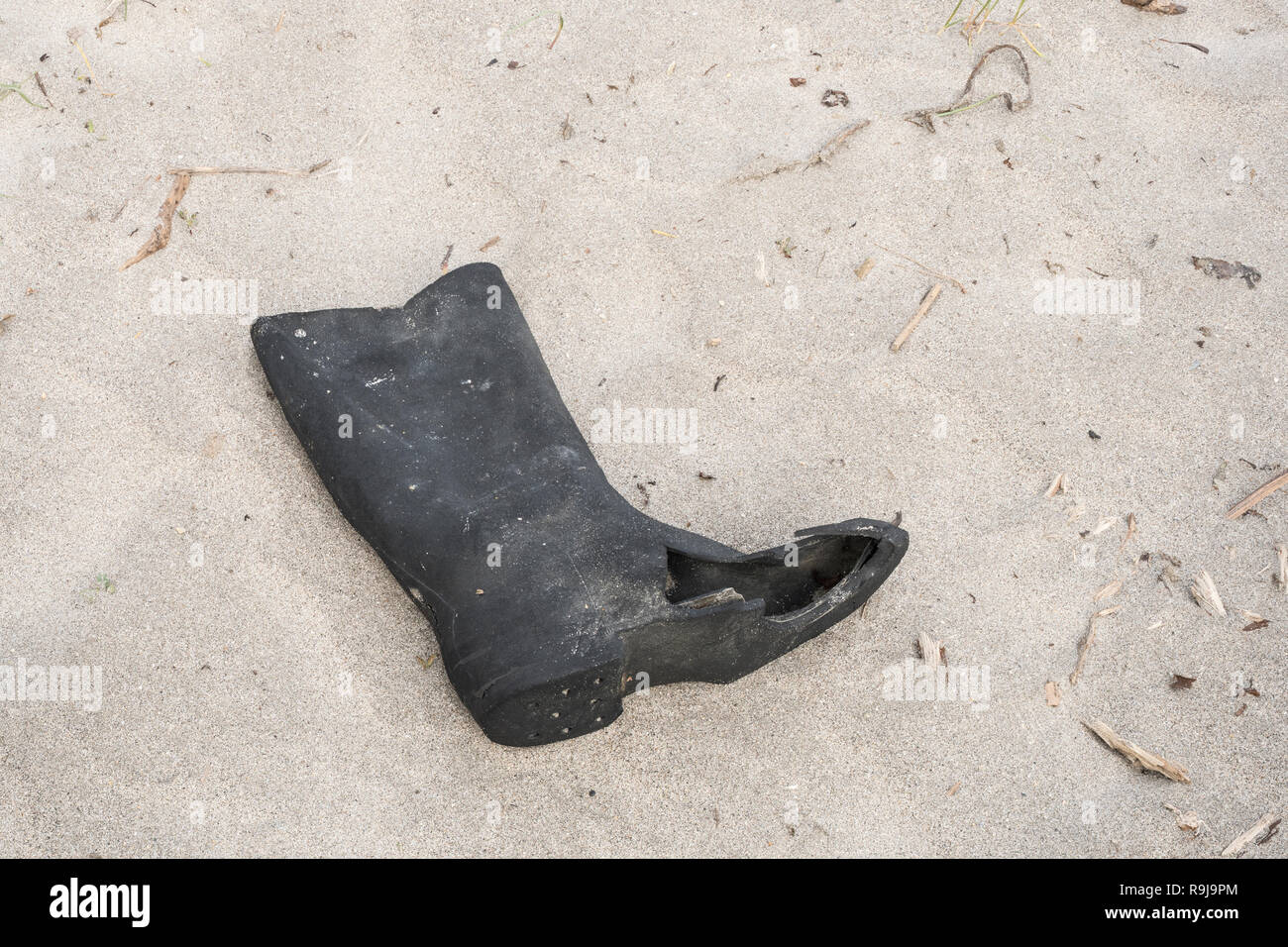 Old rubber boot washed up on shore & polluting the shoreline. Metaphor plastic pollution, environmental pollution, war on plastic, old footwear. Stock Photo