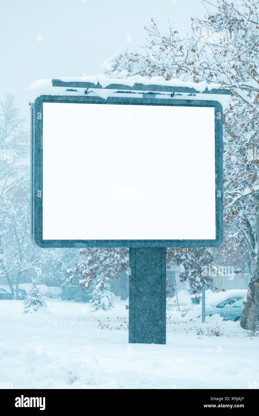 Empty billboard poster advertisement mock up on snowy street. Outdoor advertising for winter season in urban city area. - Stock Image