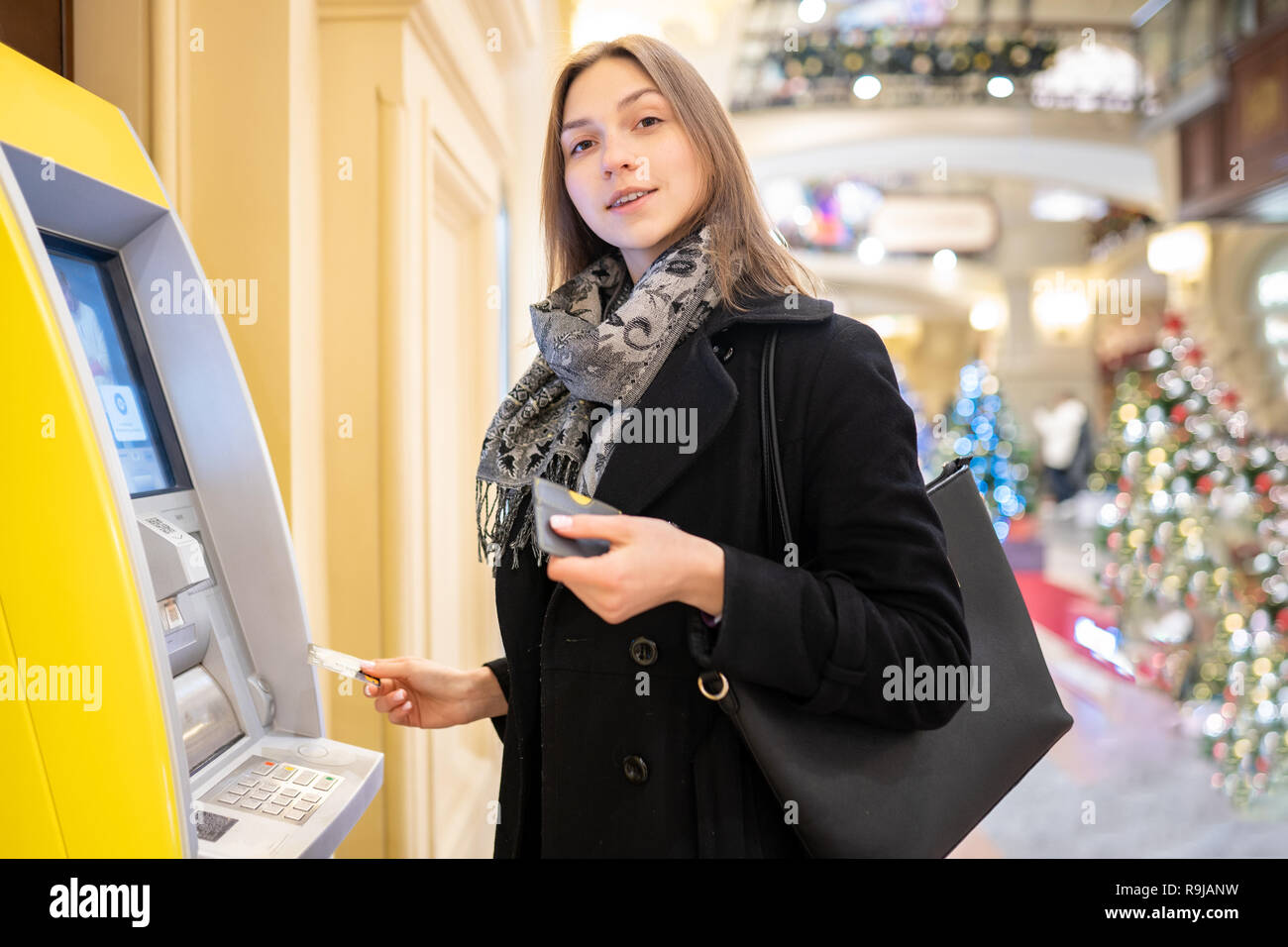 Image of happy brunette with bank card at ATM on blurred background - Stock Image