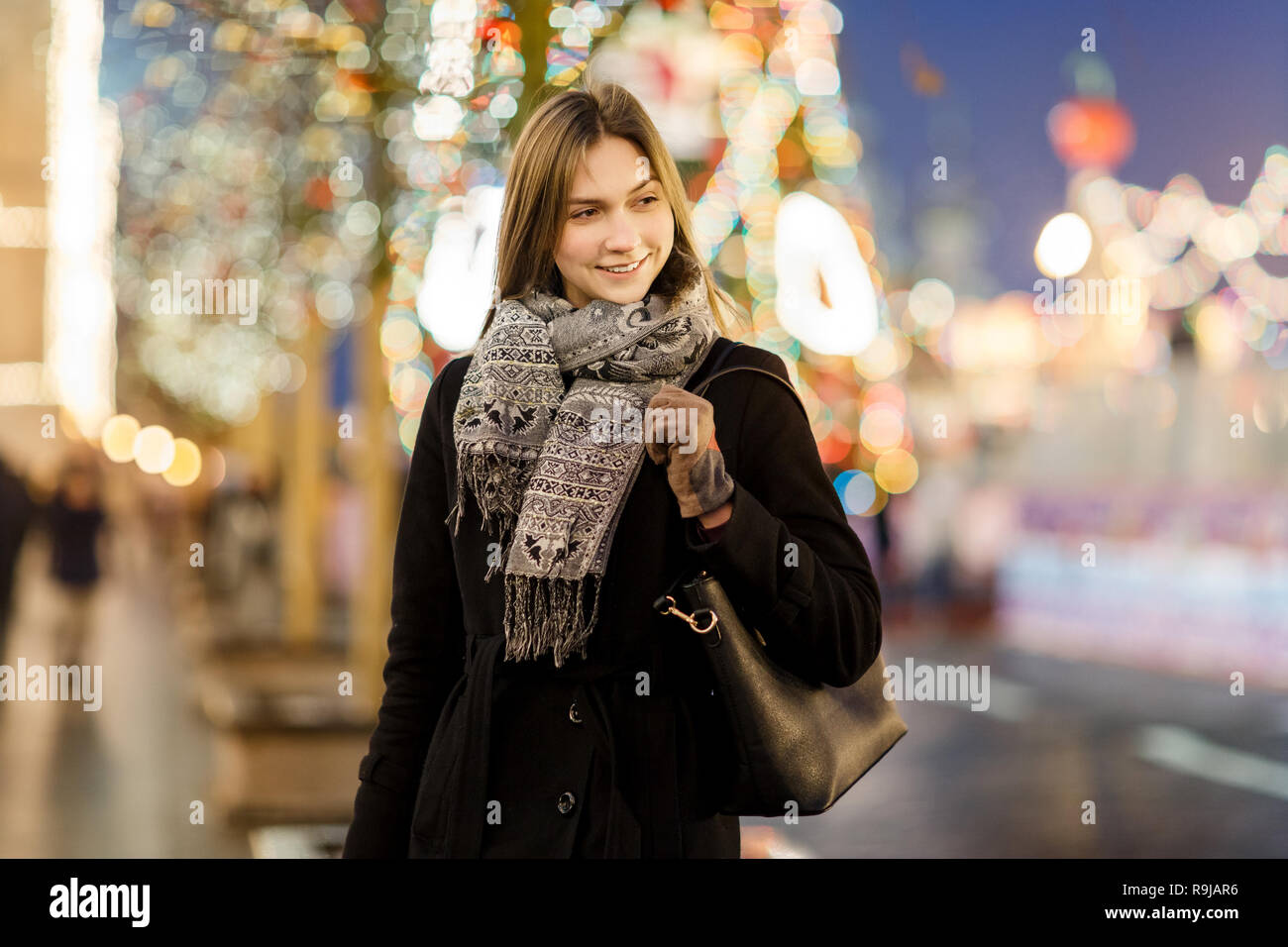Photo of woman outside in city on blurred background with garland - Stock Image