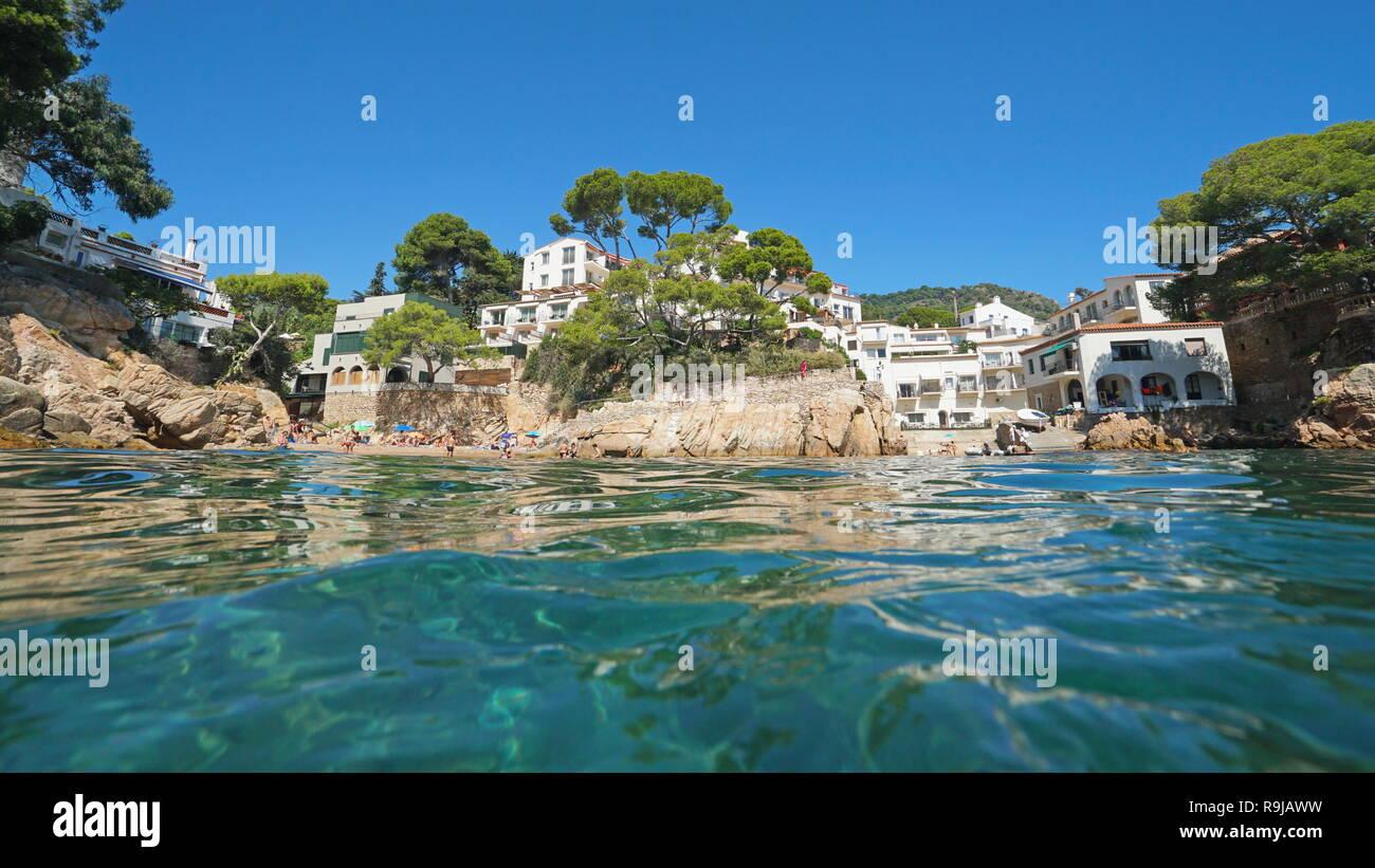 Spain rocky coastline with small beach of the Mediterranean village Fornells de Mar, seen from sea surface, Begur, Catalonia, Costa Brava - Stock Image