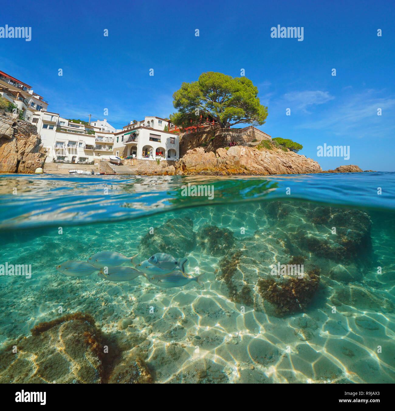 Spain Costa Brava picturesque Mediterranean village and fish underwater, Fornells de Mar, split view half above and below water surface, Begur - Stock Image