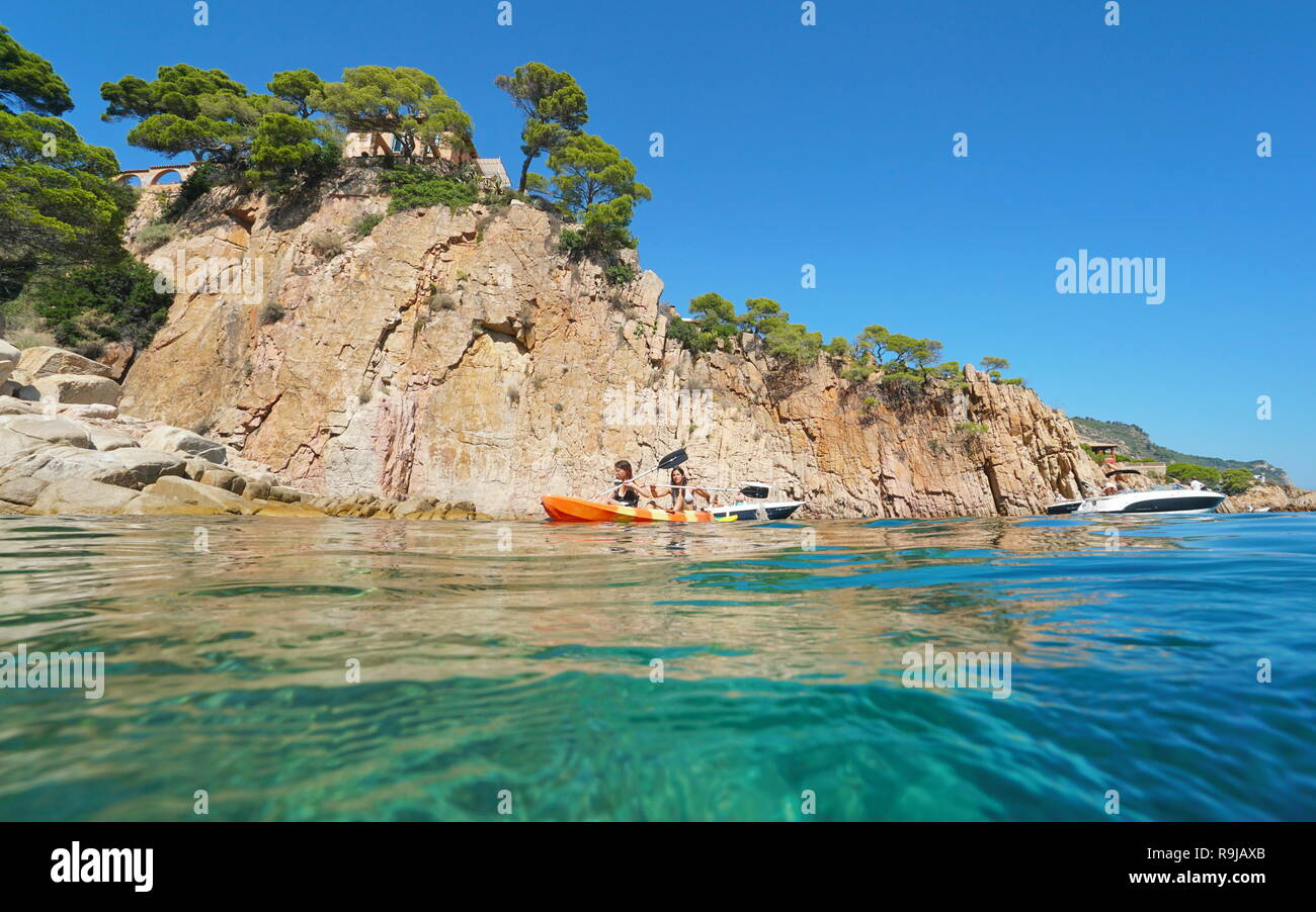Young women paddle a kayak on the Mediterranean sea in front of a rocky coastline, Aiguablava, Begur, Catalonia, Costa Brava, Spain - Stock Image