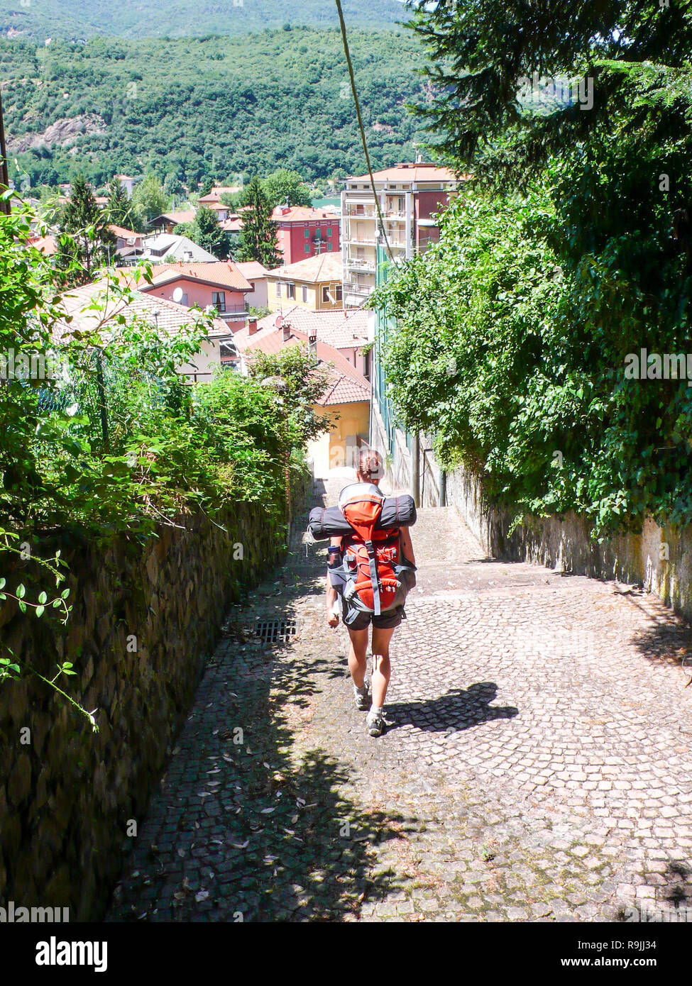 woman backpacker hikes into a mediterranean Europen village - Stock Image