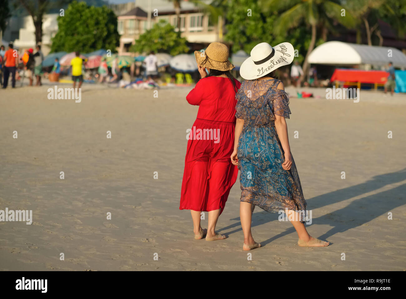 Two prettily dressed young female Chinese tourists at Patong Beach, Phuket, Thailand, observing the scenery - Stock Image