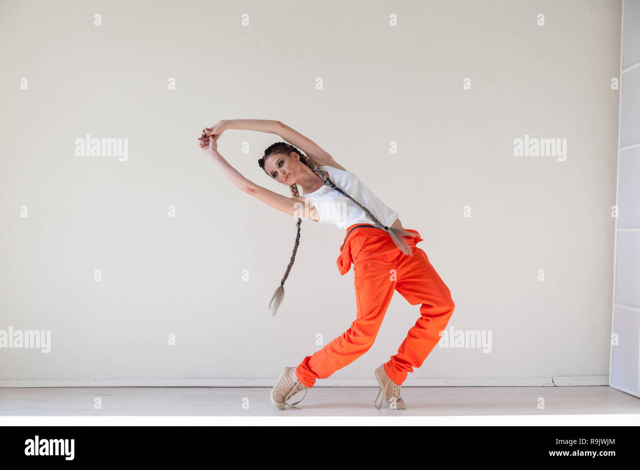 woman with braids dancing to the music - Stock Image