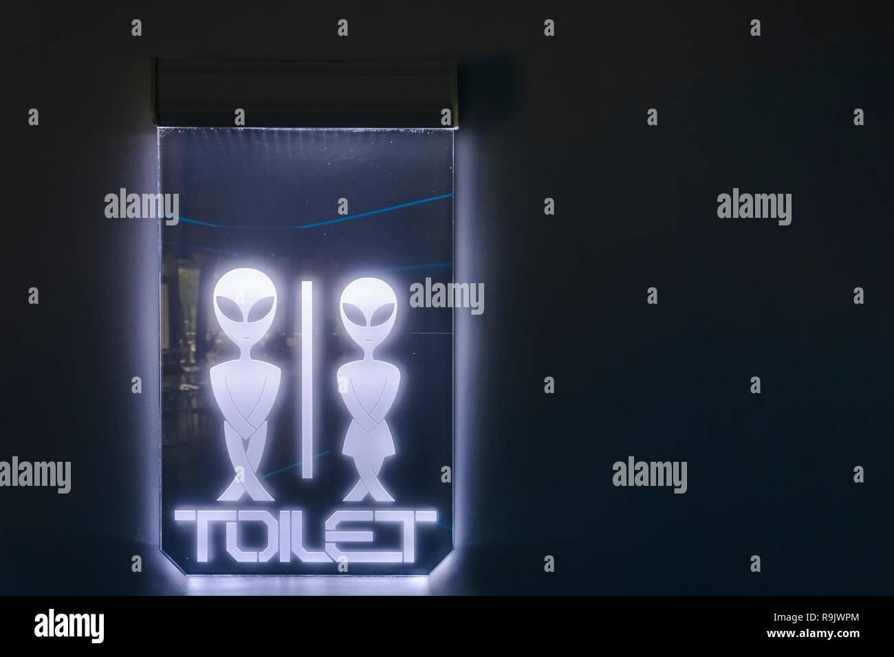Illuminated alien sign, futuriistic alien toilet sign Stock Photo