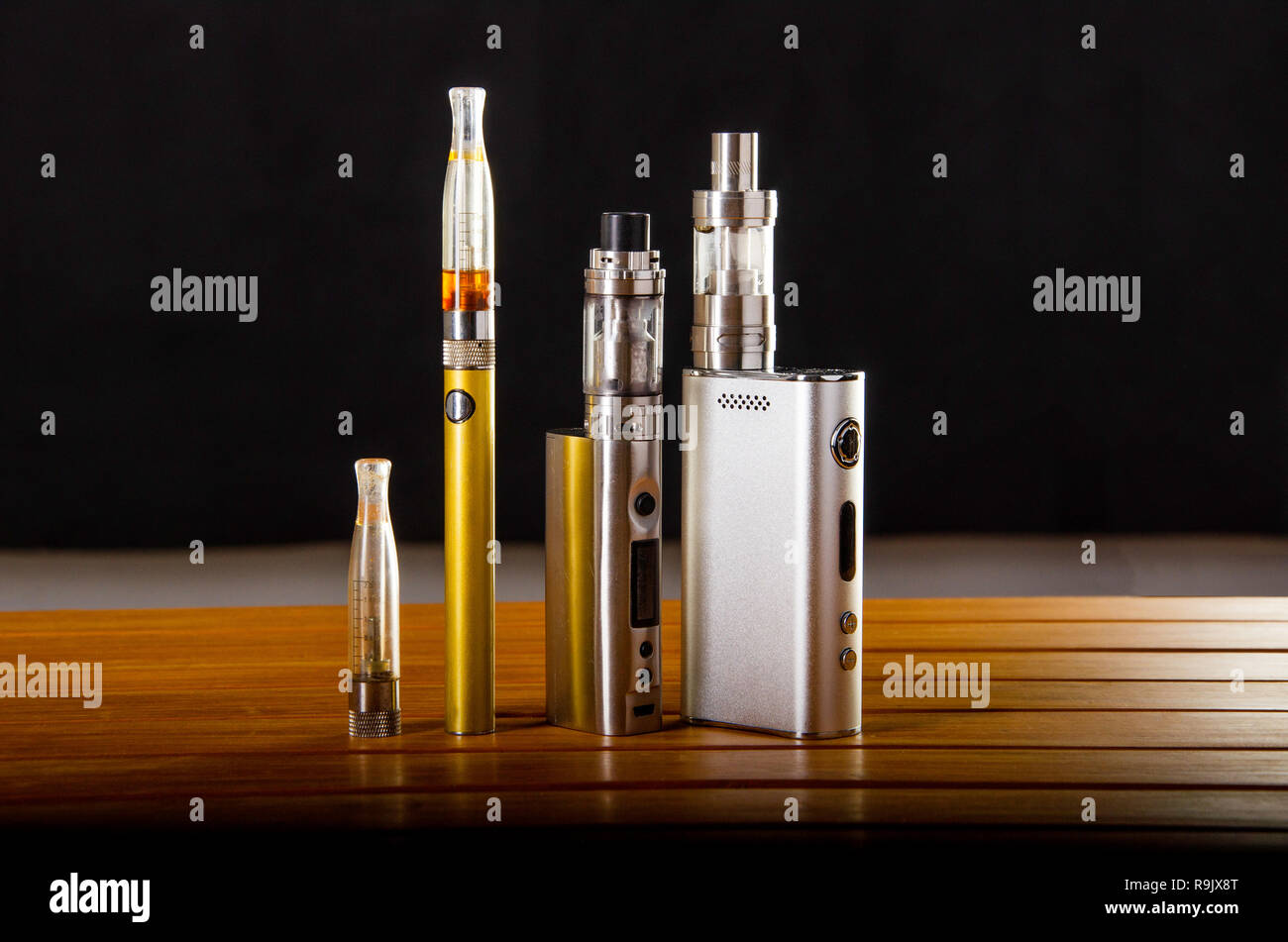 Popular vaping e cig devices mod.electronic cigarette over wooden background. vaporizer e-cig old device model. Stock Photo