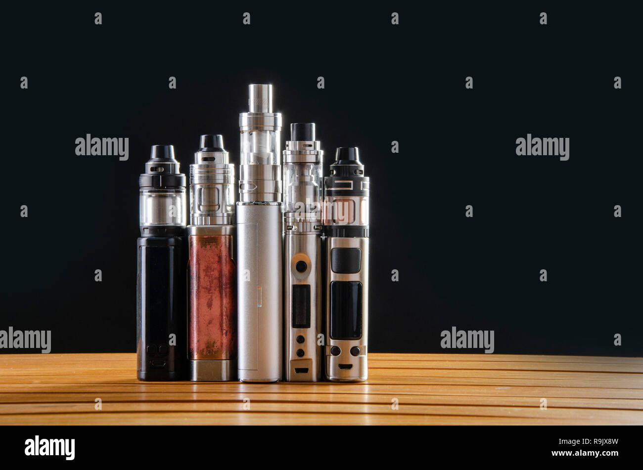 Popular vaping e cig devices mod.electronic cigarette over wooden background. vaporizer e-cig old device model. - Stock Image