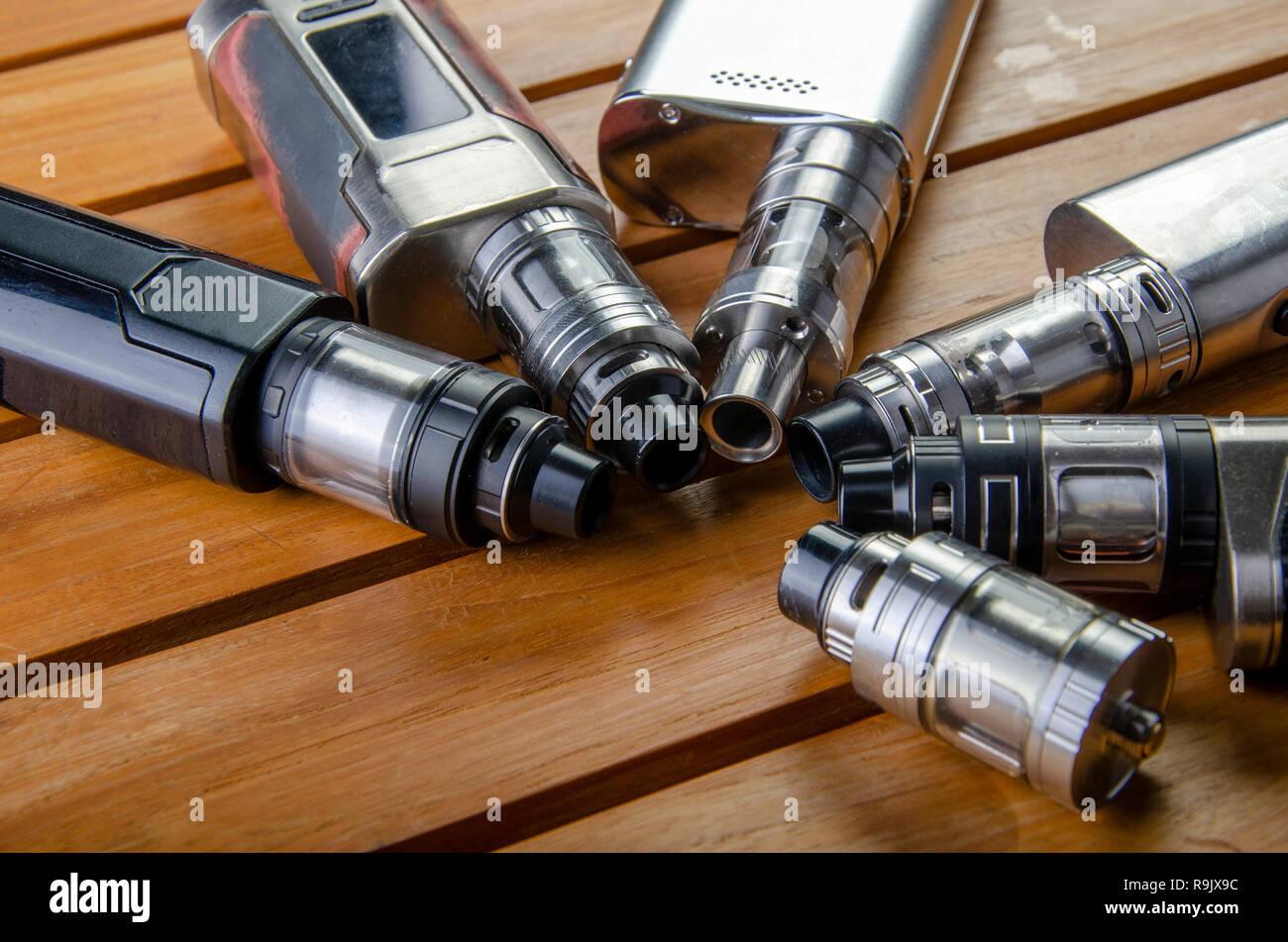 Popular vaping e cig devices mod.electronic cigarette over wooden background. vaporizer e-cig old device model. Stock Photo