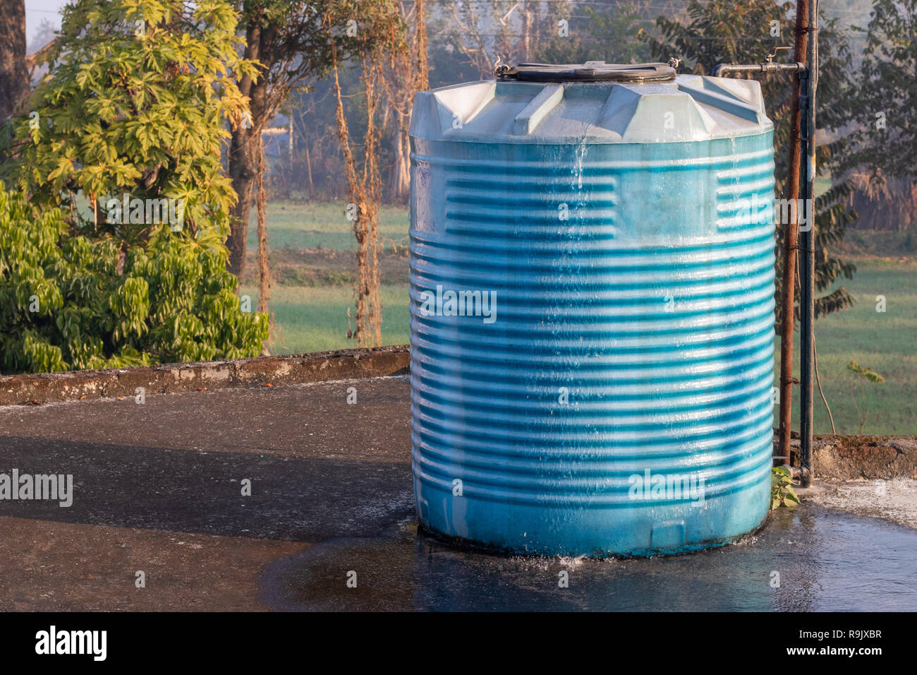 Water tank overflowing, wasting water - Stock Image
