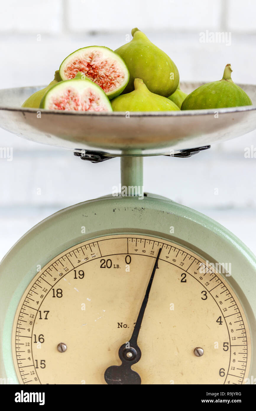 Retro / antique kitchen scale and ripe, halved figs on natural wood table - Stock Image