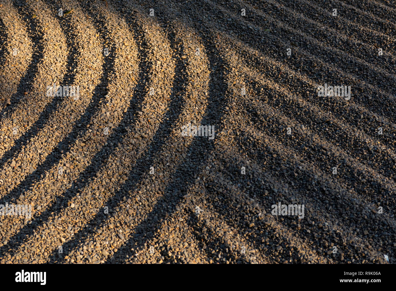 Raked garden pebbles in sunlight in Japan - Stock Image