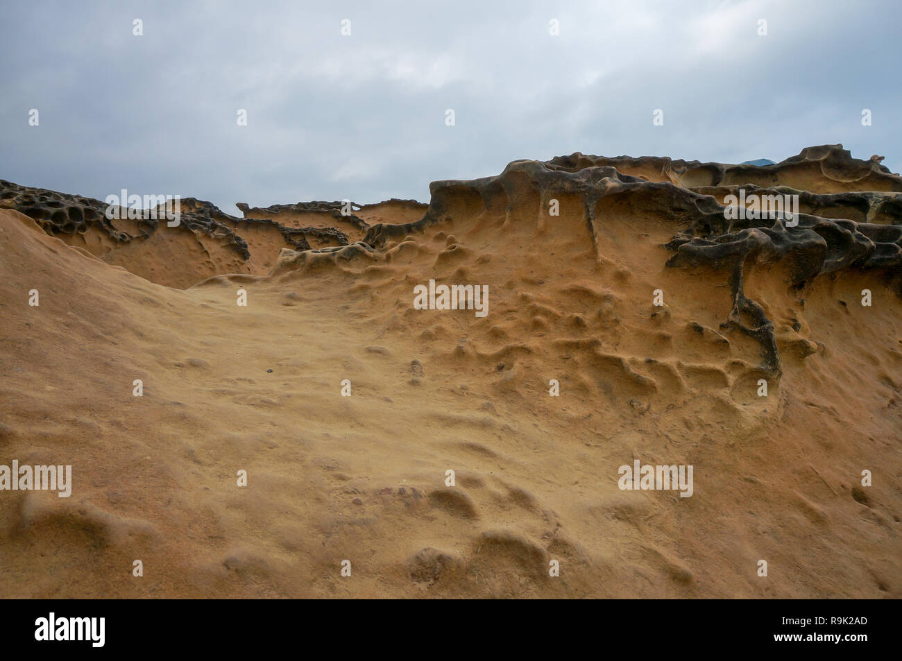 Unique geological formations at Yehliu Geopark in Taiwan on a sunny day with a blue sky with some clouds - Stock Image