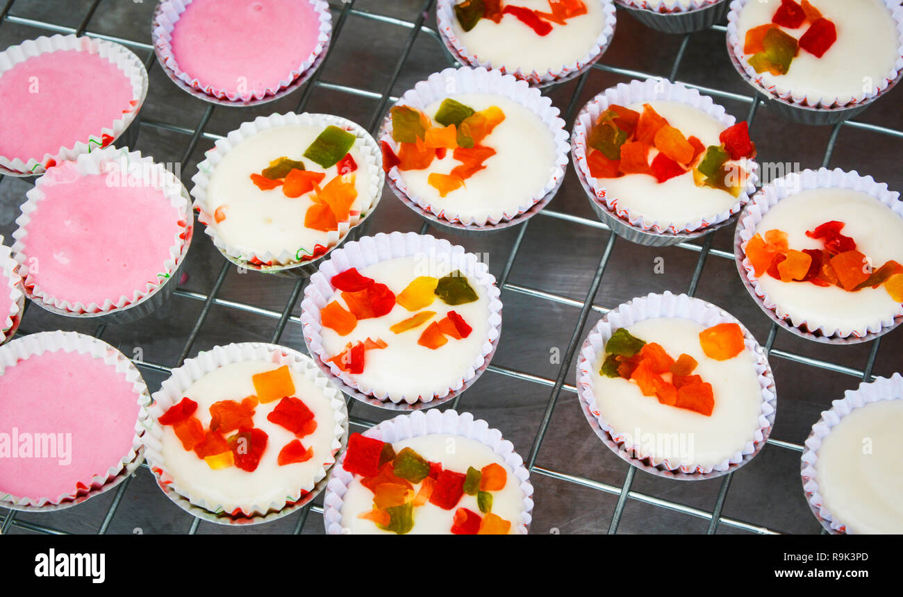 Raw fluffy rice flour cake for Steamed / White and pink flour cake sweet dessert topped with dry fruit - Stock Image